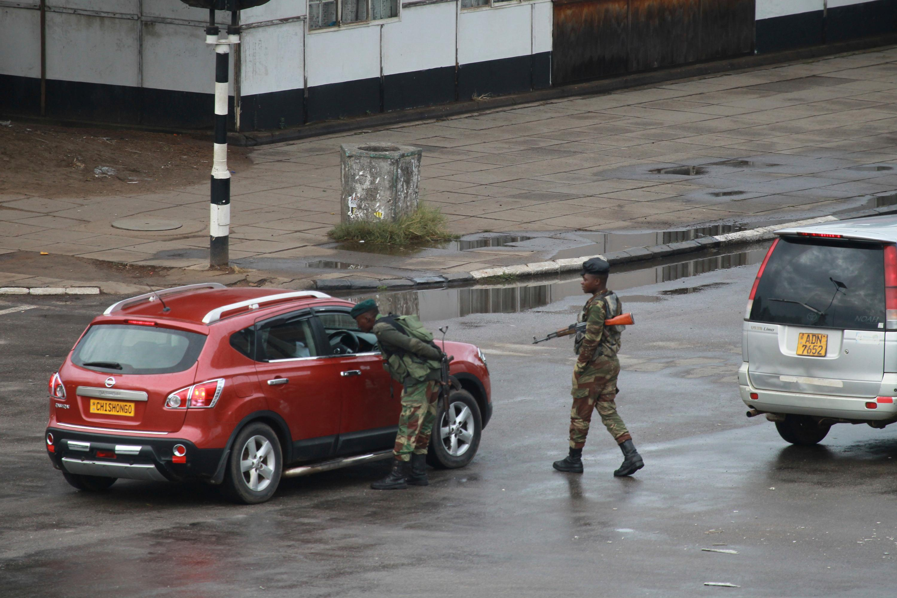 "Armed soldiers stop a vehicle to search on the road leading to President Robert Mugabe's office in Harare, Zimbabwe Wednesday, Nov. 15, 2017. Overnight, at least three explosions were heard in the capital, Harare, and military vehicles were seen in the streets. On Monday, the army commander had threatened to ""step in"" to calm political tensions over the 93-year-old Mugabe's possible successor. (AP Photo/Tsvangirayi Mukwazhi)"