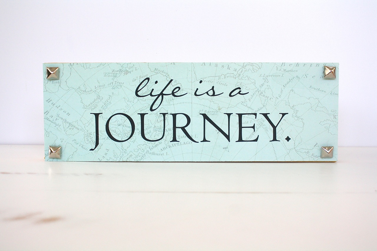 "Life is a Journey Art: We can all use a little reminder to keep us feeling encouraged. Put together this Life is a Journey piece with a canvas measuring 3"" x 12"", a piece of travel themed scrapbook paper, ""Life is a Journey"" vinyl from Decorating Your Life, wood stain, craft glue and metal brads.  Paint the canvas with the wood stain. Cut a piece of scrapbook paper to 3"" x 12"". Glue it to the canvas. Next, add the vinyl words. Finish by gluing the metal brads in the corners. (Image: Malia Karlinsky / Seattle Refined)"