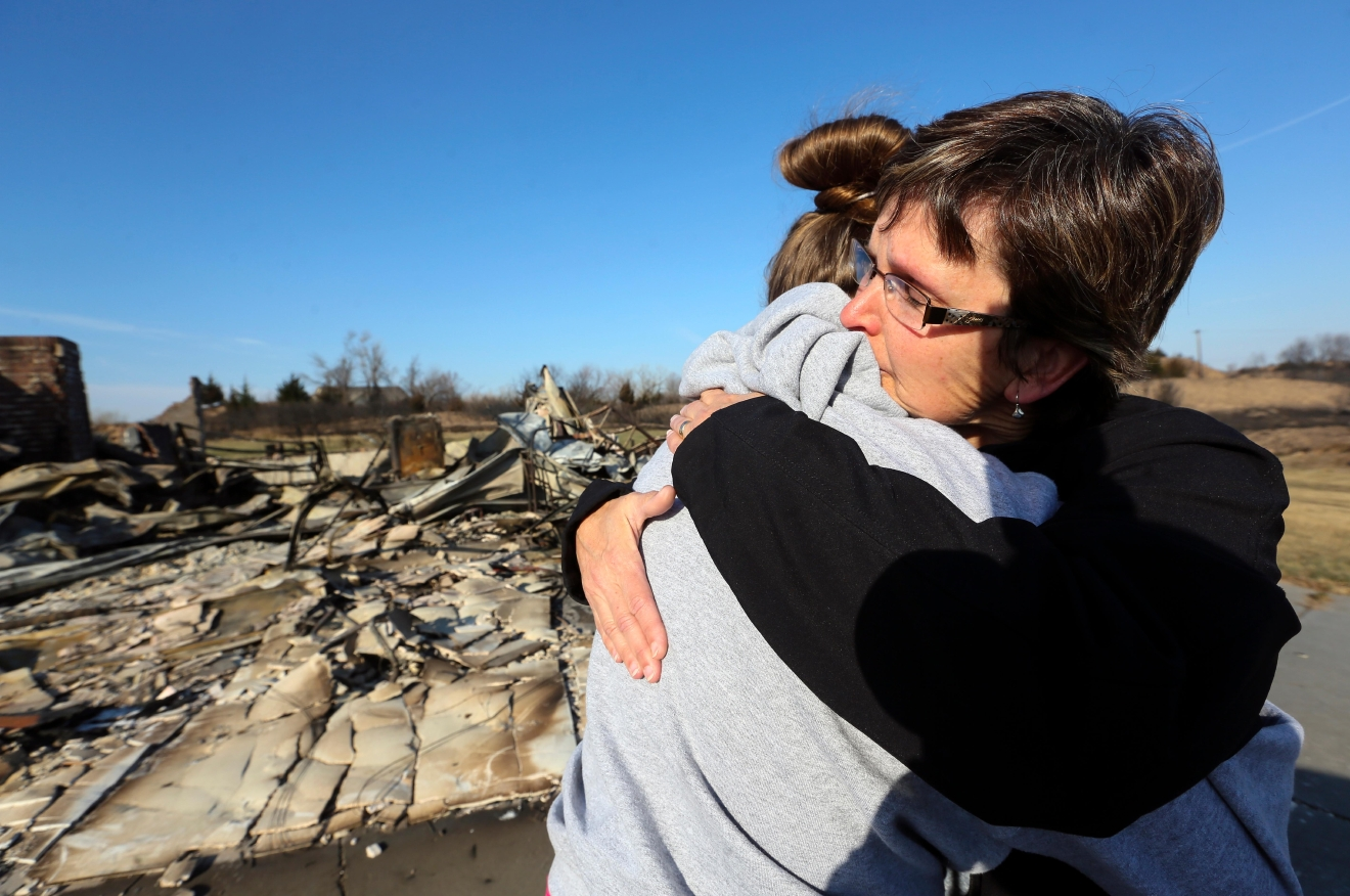 Zane Jackson embraces her daughter, Shelby Jackson, as they arrive to see their destroyed home for the first time in the Highlands subdivision on Wednesday, March 8, 2017, in Hutchinson, Kan. The home was destroyed in the wildfires Monday night. (Lindsey Bauman/The Hutchinson News via AP)