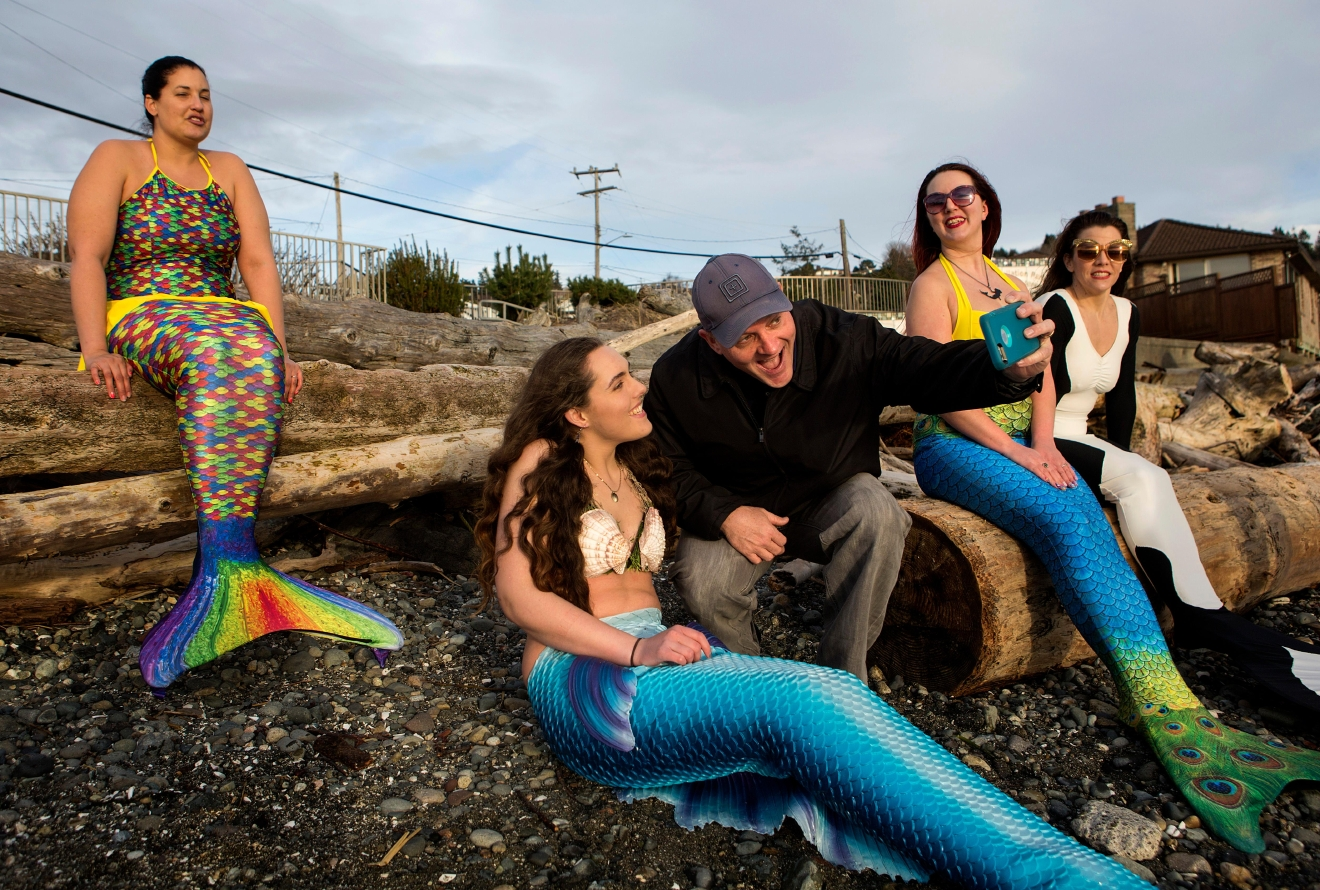 Puyallup resident John Weldon snaps a selfie with on of the mermaids after he took the trip up north with his four-year-old daughter who is obsessed with mermaids. (Sy Bean / Seattle Refined)