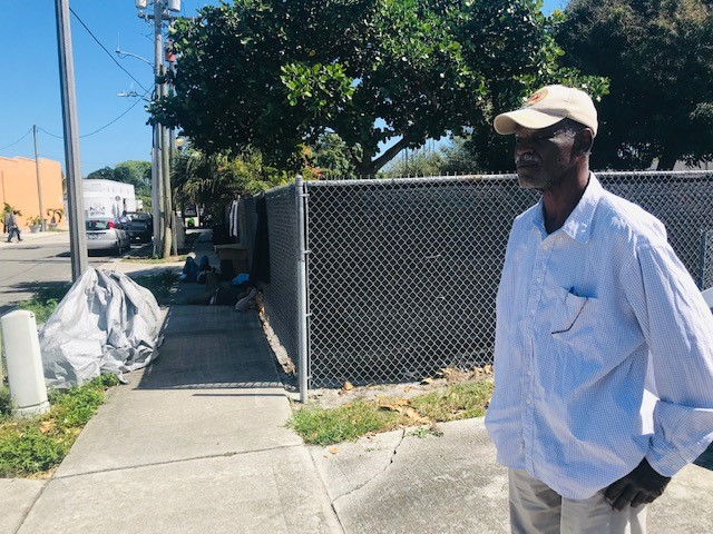 As Michael Cleveland stands in his West Palm Beach drive way, homeless men can be seen napping on the sidewalk next door.{&nbsp;} A large gray tarp, suitcases, plastic bags and cardboard are also visible on the walkway.{&nbsp;} (WPEC) <br>