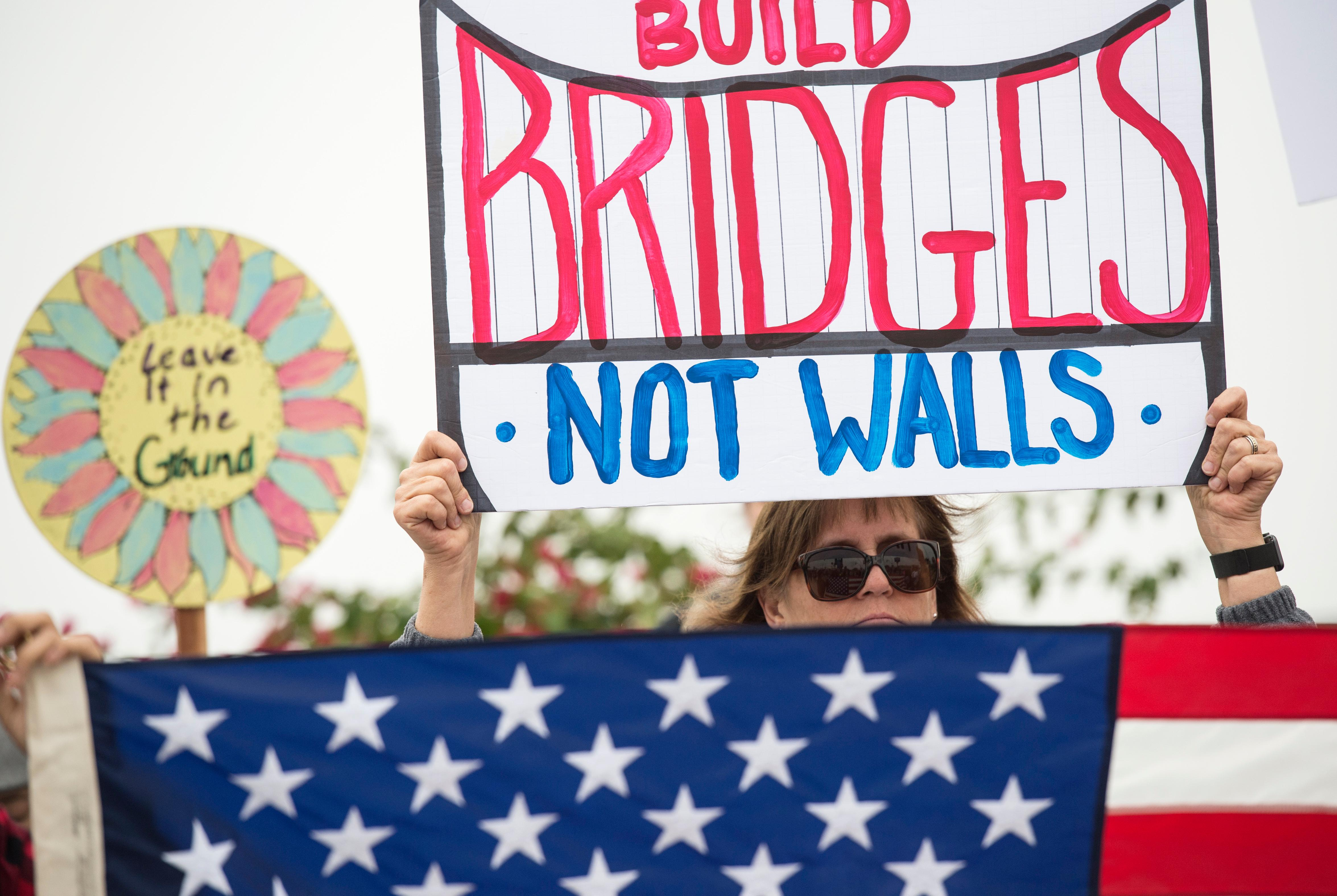 "Lauren Rees holds up a sign during a rally against a upcoming scheduled visit by President Donald Trump Tuesday, March 13, 2018, in San Diego.  Protesters chanted, ""No ban! No wall!"" near the San Ysidro border crossing, where tens of thousands of people enter the U.S. daily from Tijuana, Mexico, many on their way to work or school in San Diego.  (AP Photo/Kyusung Gong)"