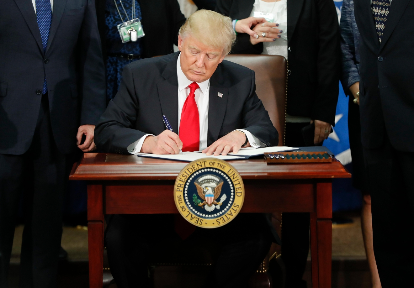 President Donald Trump signs an executive order for border security and immigration enforcement improvements, Wednesday, Jan. 25, 2017, at the Homeland Security Department in Washington.  (Photo credit: AP Photo/Pablo Martinez Monsivais)