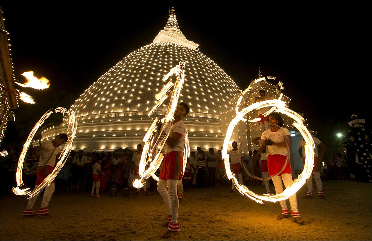 In this photo taken on Jan. 20, 2016, Sri Lankan fireball dancers are seen performing during the inauguration of the annual 'Duruthu Perahera' festival at Kelani Buddhist temple, in the outskirts of Colombo, Sri Lanka. The festival is held to commemorate Buddha's first visit to Sri Lanka about 2500 years ago. It is widely believed that Buddha visited the island nation on three occasions, spreading his doctrine that is the foundation of Buddhism, one of the world's major faiths. (AP Photo/Eranga Jayawardena)