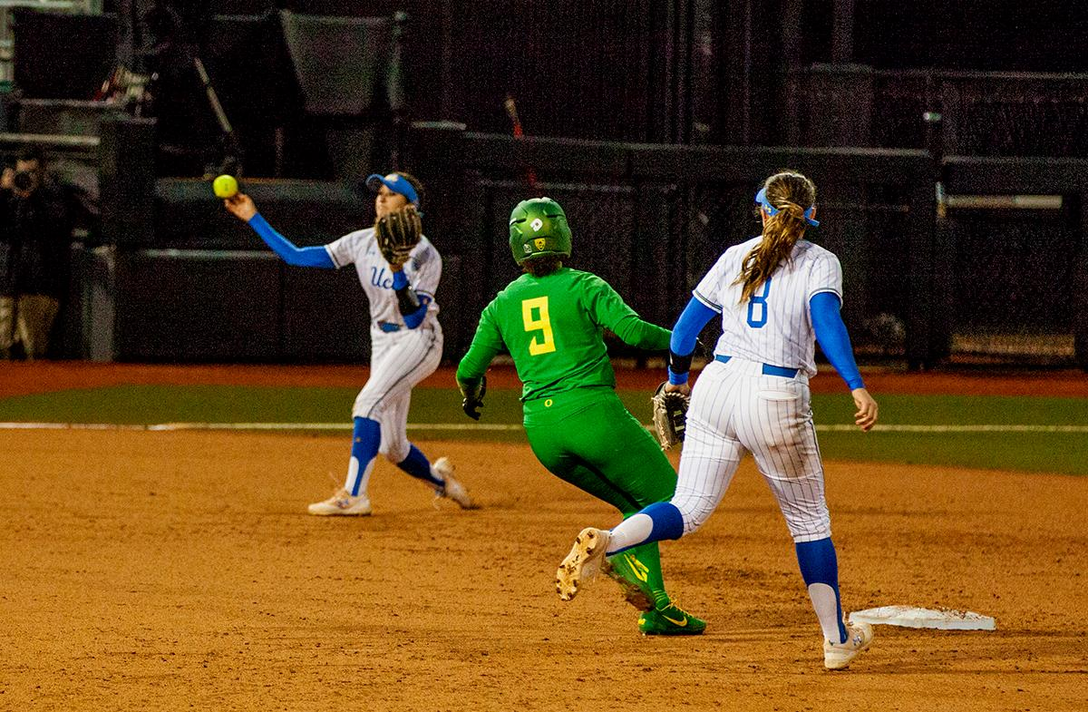 Shannon Rhodes advances to second as the UCLA player attempts to get an out at first. The University of Oregon Ducks softball pitcher Miranda Elish held the UCLA Bruins scoreless for five innings as the Ducks put seven runs on the board. The Bruins rallied with a two-run homer in the sixth and a three-run home run in the seventh, but the Ducks held on and beat undefeated UCLA 7-5 at Jane Sanders Stadium Saturday. The Ducks improved their record to 24-5. Photo by William Tierney, Oregon News Lab