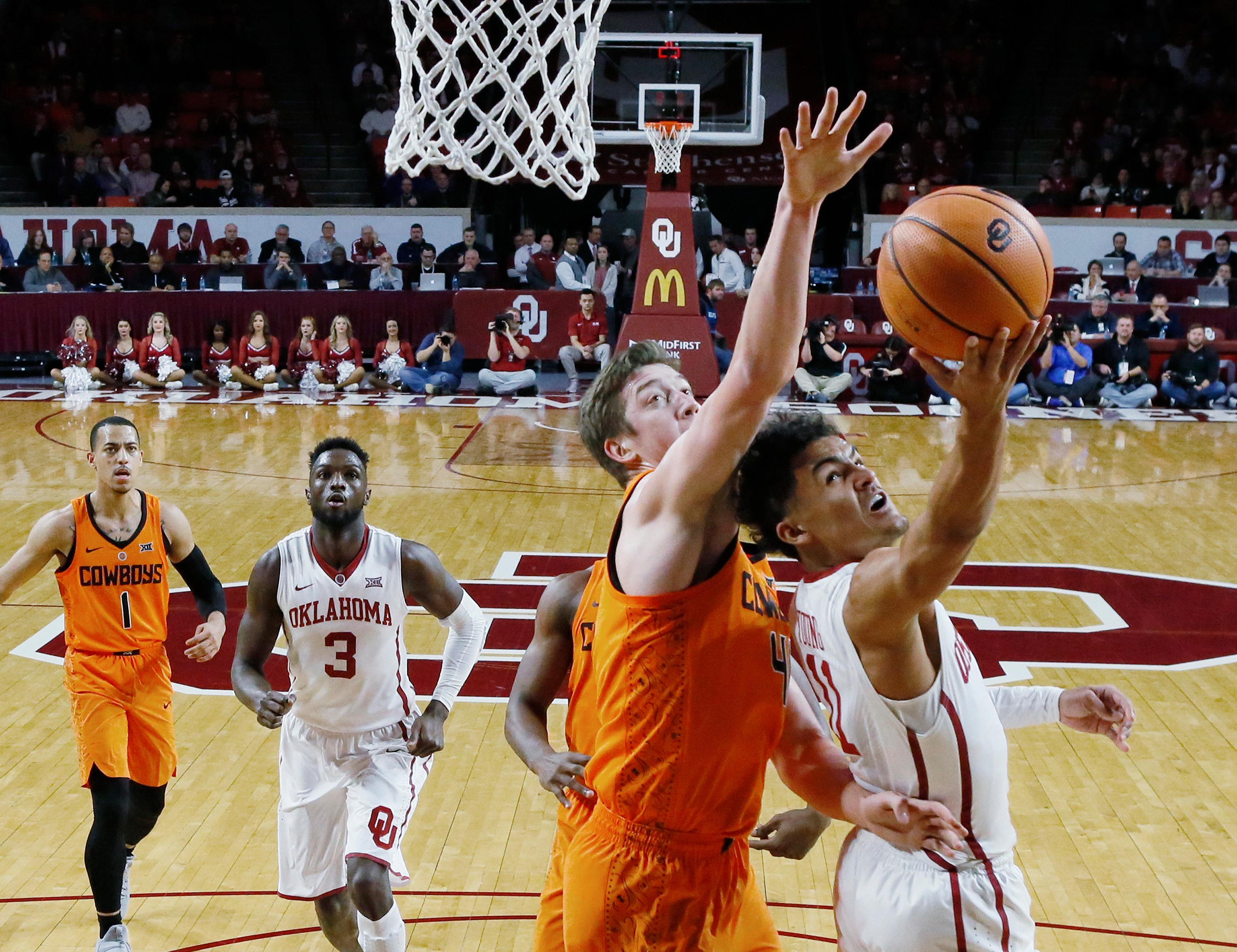 Oklahoma guard Trae Young (11) shoots as Oklahoma State forward Mitchell Solomon, left, defends during the first half of an NCAA college basketball game in Norman, Okla., Wednesday, Jan. 3, 2018. (AP Photo/Sue Ogrocki)
