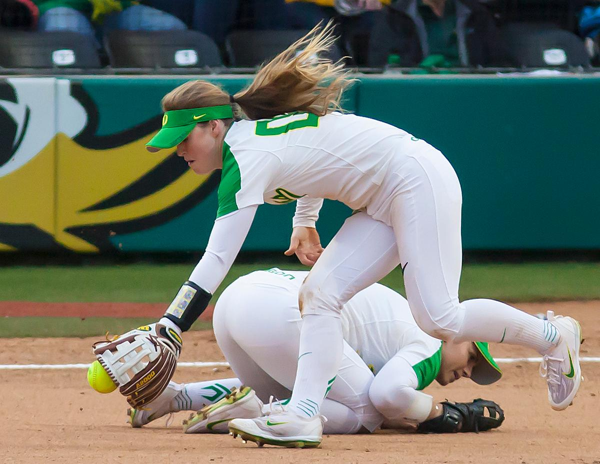 Oregon infielder Jenna Lilley (#00) scoops up a short hit before passing to the ball to first base. In the first of a three game series the Oregon Ducks defeated the California Golden Bears five to one. Photo by Ben Lonergan, Oregon News Lab