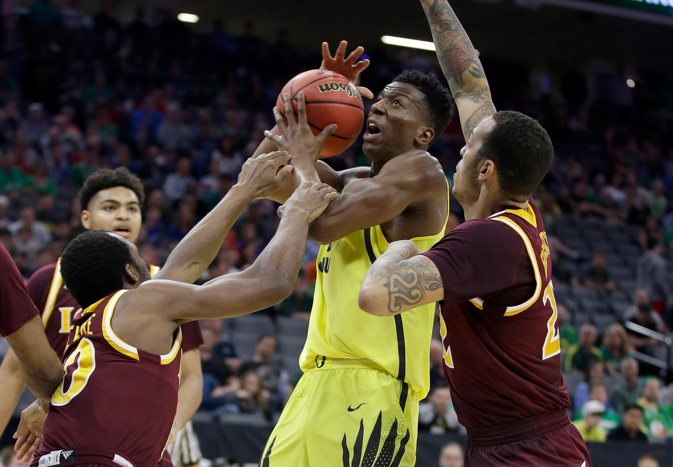 Oregon forward Kavell Bigby-Williams, center, is fouled by Iona guard Jon Severe, left, during the first half of a first-round game in the men's NCAA college basketball tournament Sacramento, Calif. Friday, March 17, 2017. (AP Photo/Rich Pedroncelli)