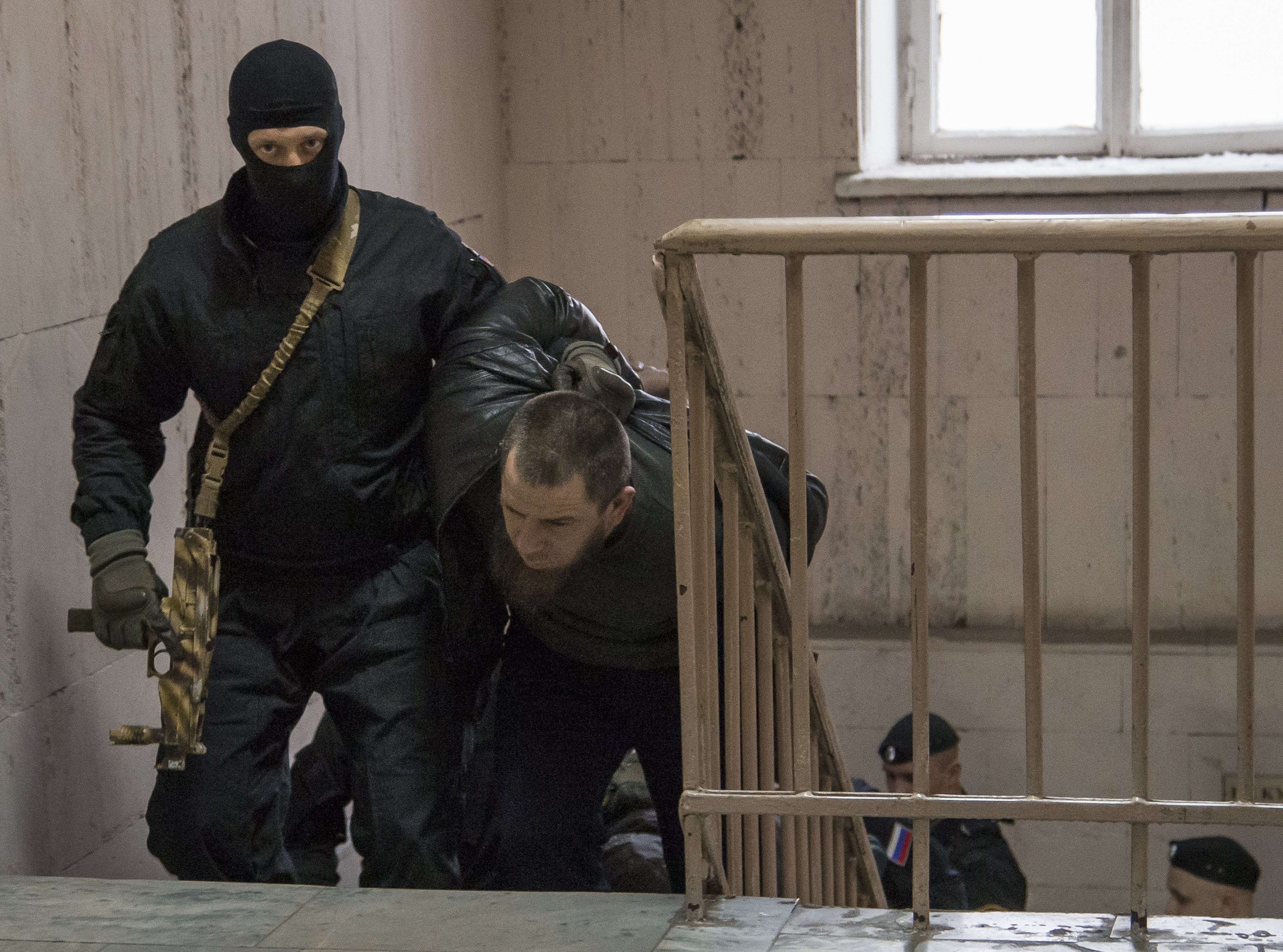 ADDING NAME OF MAN- Police escort Tamerlan Eskerkhanov believed to be one of five suspects in the killing of Boris Nemtsov in a court room in Moscow, Russia, Sunday, March 8, 2015. Five suspects in the killing of prominent Russian opposition figure Boris Nemtsov have been delivered to the court for arraignment, the spokeswoman for a Moscow court said Sunday. The statement by Anna Fedeeva to reporters outside the courthouse came one day after the Federal Security service said two suspects had been detained. Russian news agencies late Saturday reported that two others had been detained, and Investigative Committee spokesman Vladimir Markin said Sunday there was a fifth suspect. Details remain vague in the case despite President Vladimir Putin's pledge to pursue the killers vigorously. (AP Photo/Ivan Sekretarev)