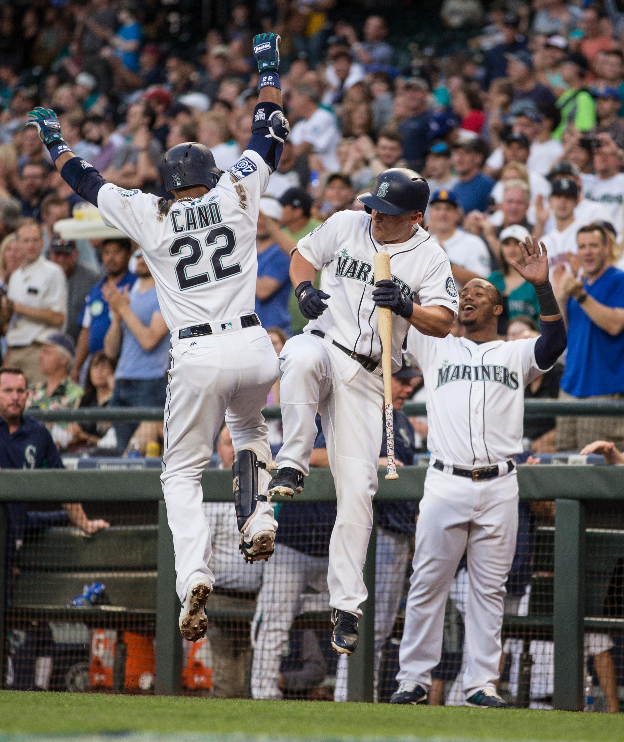 Seattle Mariners' Kyle Seager, center, Robinson Cano, left, and Jean Segura celebrate a two-run home run by Cano off of Oakland Athletics starting pitcher Jharel Cotton during the third inning of a baseball game Saturday, Sept. 2, 2017, in Seattle. (AP Photo/Stephen Brashear)