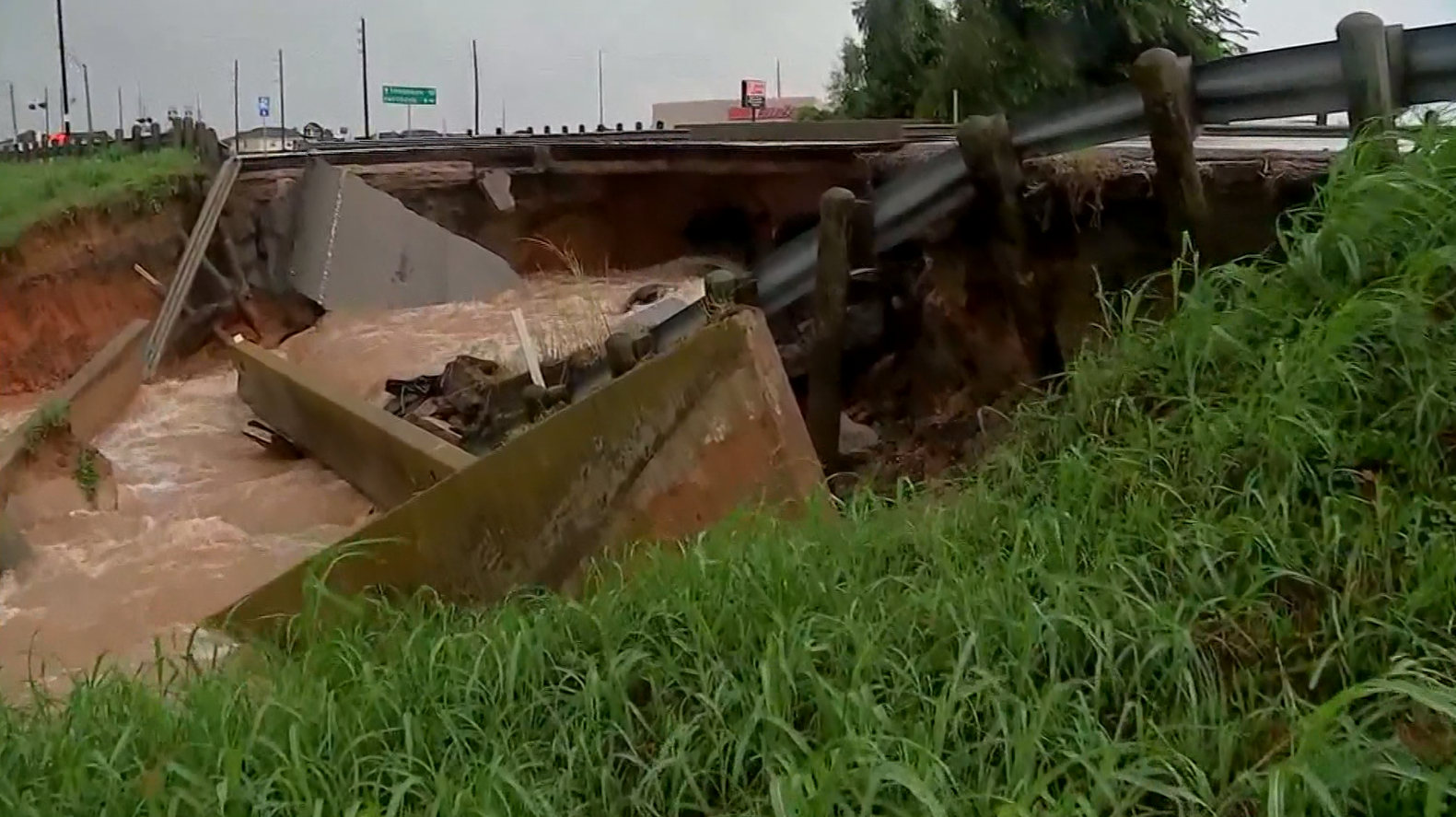 Washed out road near raging flood waters in Rosenberg, TX (KTRK/CNN)